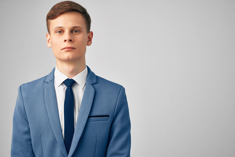 Portrait of young man standing against gray background