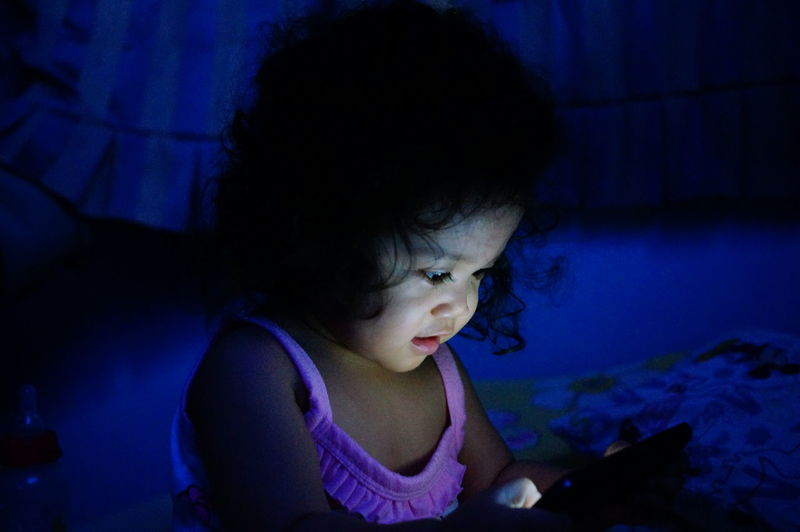 Close-up of girl using mobile phone on bed at home