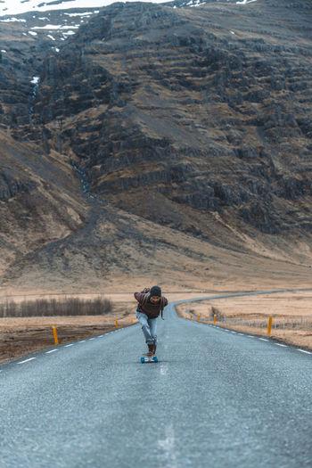 Side view of man skateboarding on road against sky