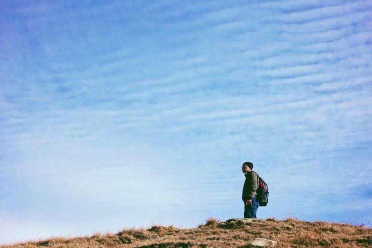 Man standing on field against sky