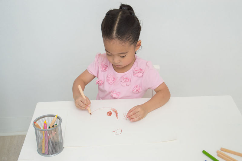 Childhood Child Indoors  Girls Innocence One Person Table Females Women Front View Pink Color Art And Craft Paper Real People Looking Lifestyles Cute Holding