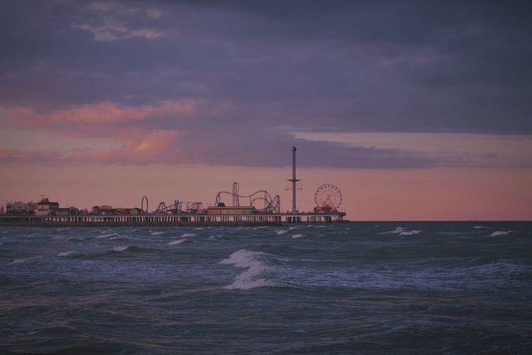 Galveston island historic pleasure pier over sea against cloudy sky