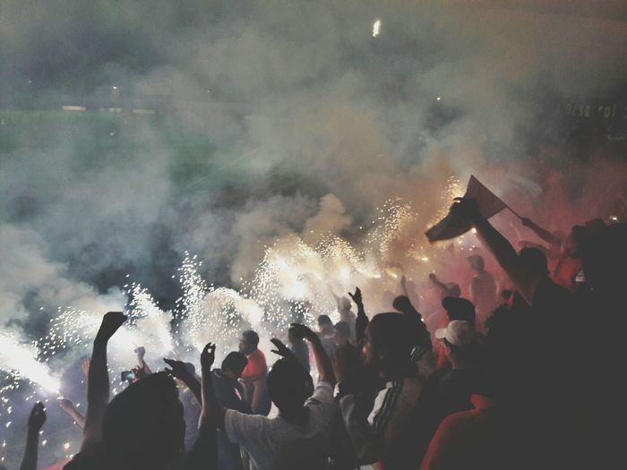 Crowd Burning Crackers In Soccer Stadium At Night