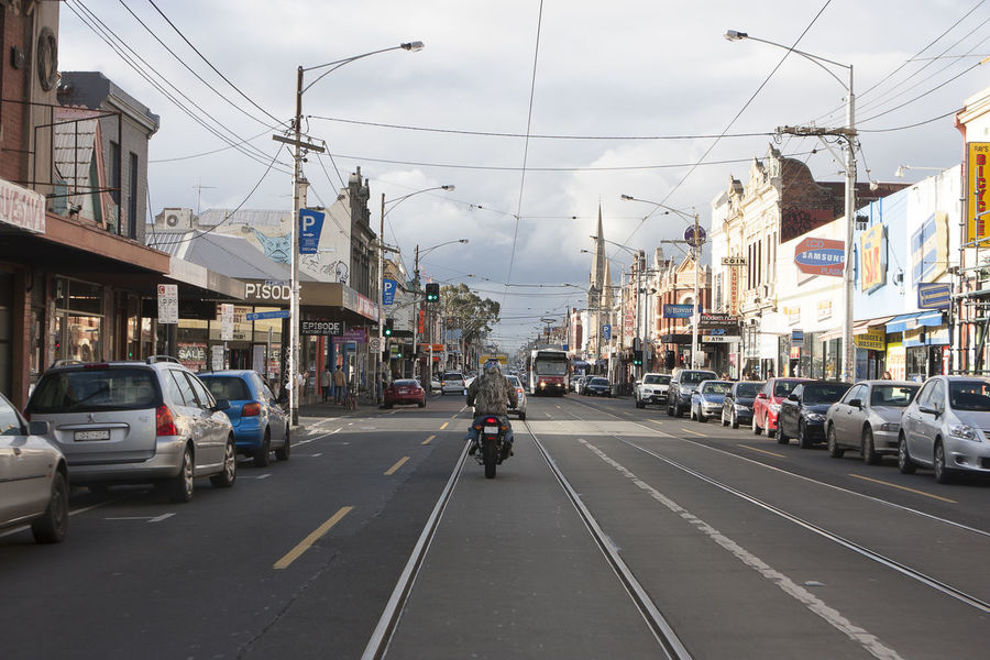 Sydney Road Architecture Building Exterior Car City City Life City Street Composition Incidental People Land Vehicle Leading Mode Of Transport Motorbike Perspective Road Sidewalk Speed Storm Clouds Street The Way Forward Tram Transportation Urban Walking