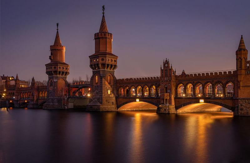 Arch bridge over river at night
