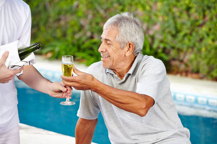 Rear view of man drinking water in swimming pool