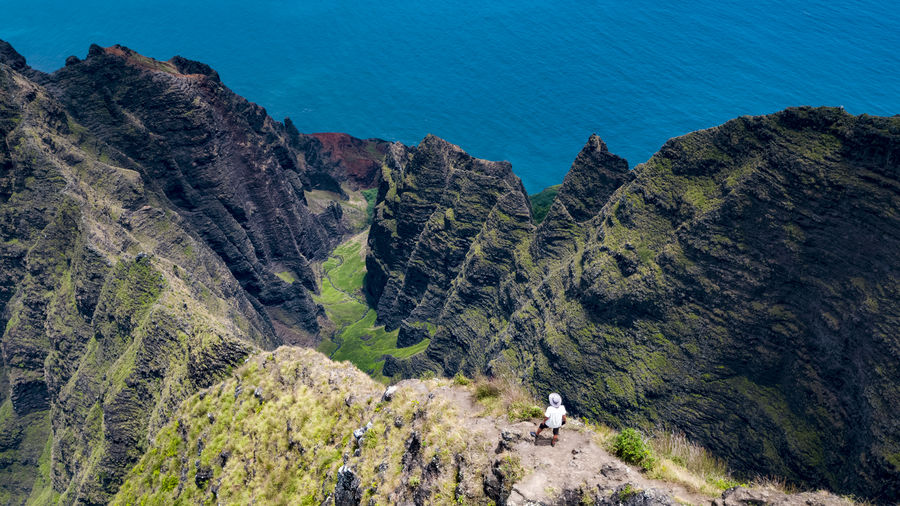 Hiking the Na Pali Coast Hiking Hawaii Napali Coast Ocean Water Sea Man Model One Person Hat Island Nature Nā Pali Coast State Park Valley Mountain Sky Landscape Mountain Range Scenics Aerial View Countryside Mountain Peak The Traveler - 2018 EyeEm Awards The Great Outdoors - 2018 EyeEm Awards