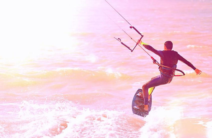 Kitesurfer at sunlight. Back view. Unrecognizable Adult Adventure Freedom Jumping Kite Kiteboard Kitesurfing One Person Outdoors Summer Sunlight Sunset Vacations Water