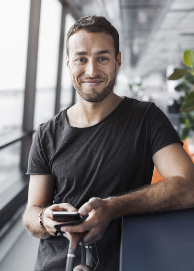 Portrait of smiling man holding mobile phone