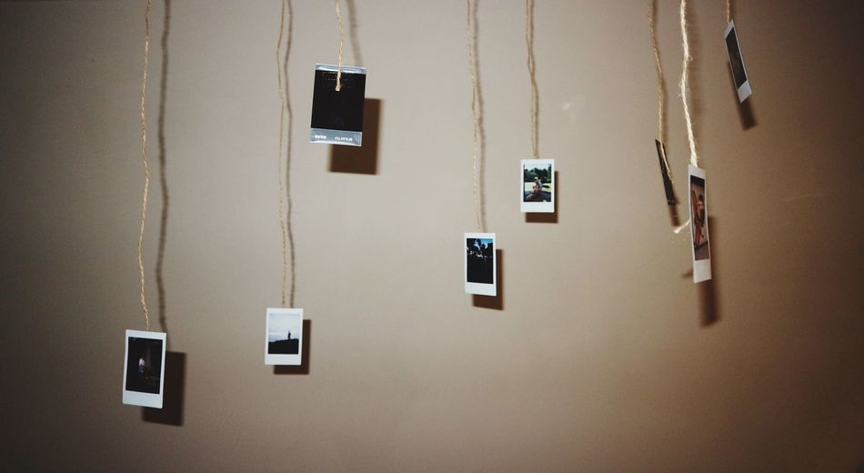 Close-up of photos hangings against wall at home