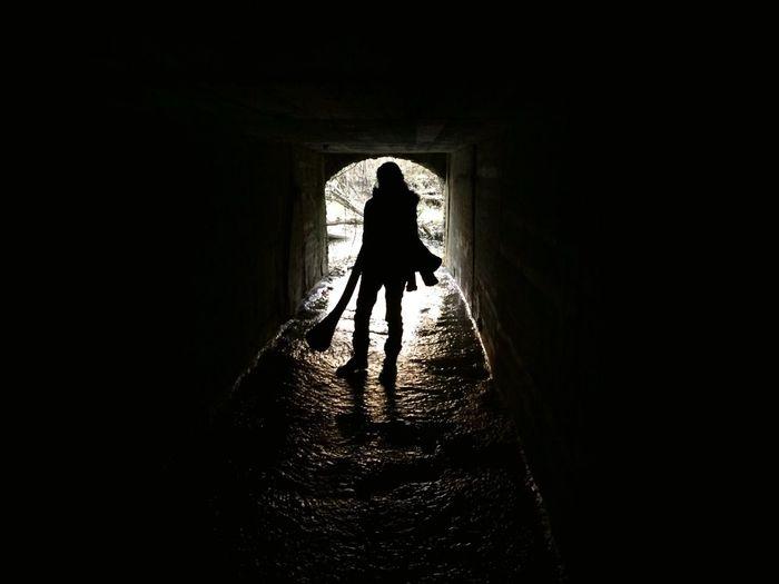 Silhouette of man walking in tunnel