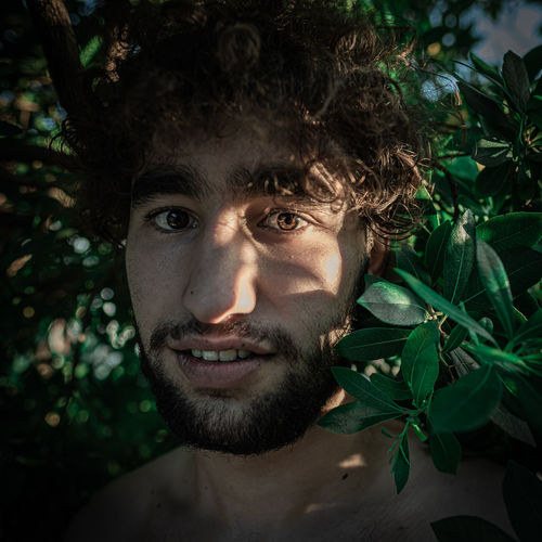Portrait of young smiling man standing by plants