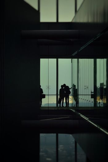 Silhouette couple standing against glass wall at airport