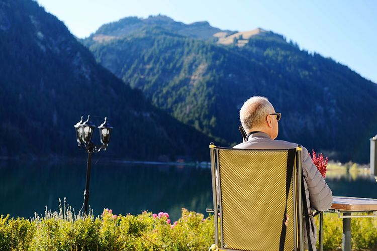 Rear view of man sitting by lake and mountains