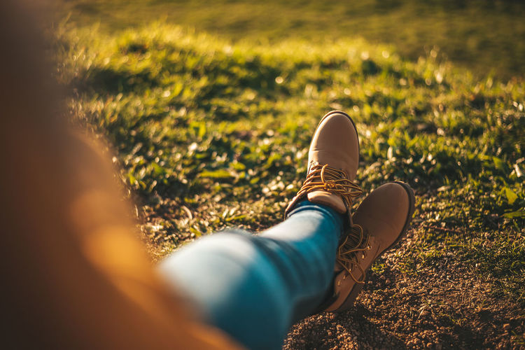 Low section of woman wearing shoes relaxing on field