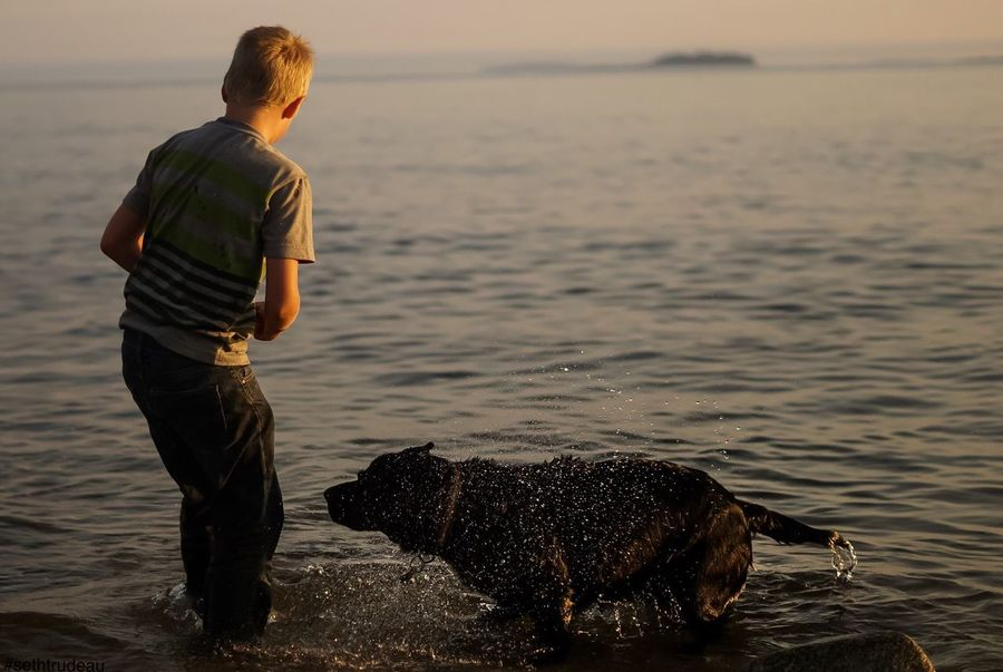 Boy with his dog One Animal Water Pets Dog Standing Domestic Animals Rear View Full Length Lifestyles Water Sethtrudeau Photography Youth Play Playing Fetch Leisure Activity Men Mammal Focus On Foreground Outdoors Nature Tranquility Sea Looking