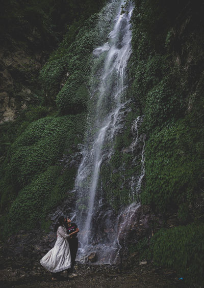 Woman on waterfall in forest