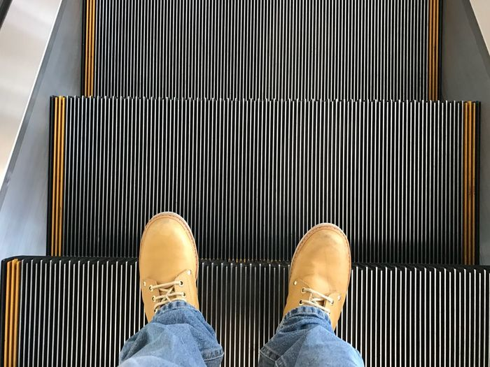 Low section of man standing on escalator