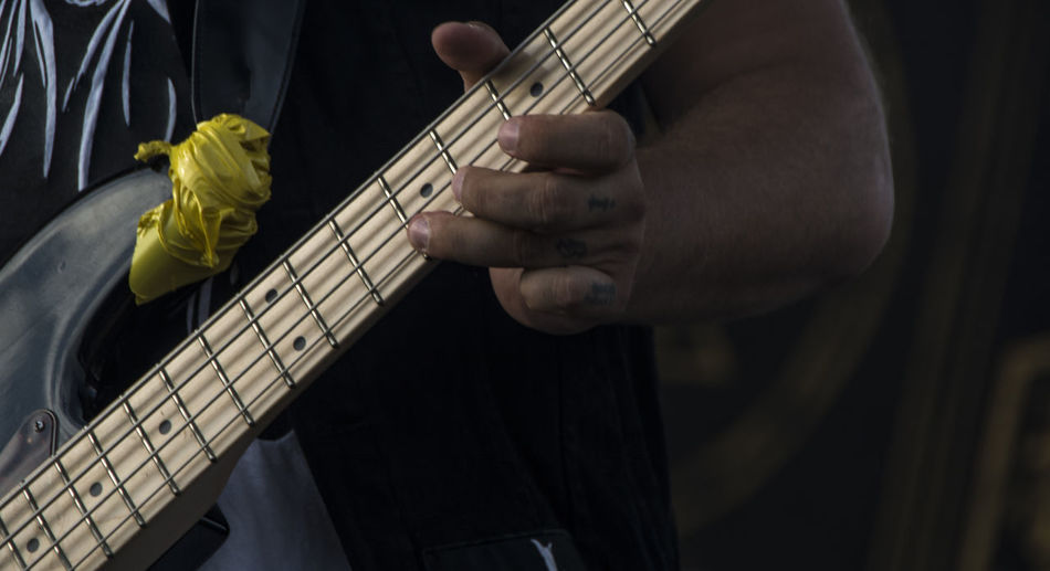 Artist Arts Culture And Entertainment Bass Guitar Close-up Electric Guitar Finger Guitar Hand Holding Human Body Part Human Hand Midsection Music Musical Equipment Musical Instrument Musician One Person Performance Playing Plucking An Instrument Skill  Stage String Instrument