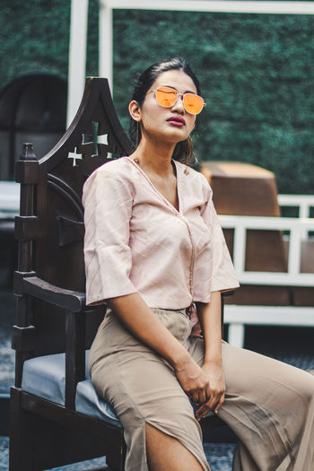 Young woman wearing sunglasses while sitting outdoors