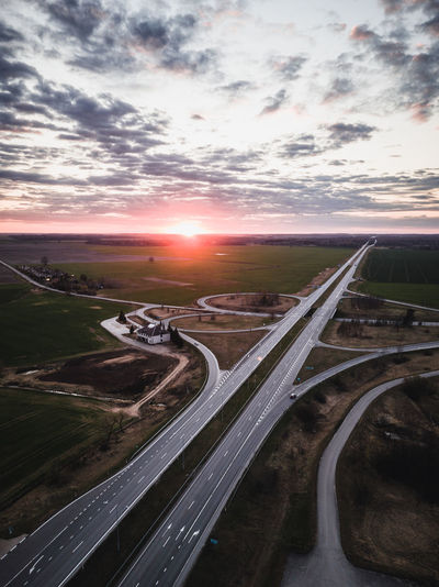 Aerial view of highway in city against sky during sunset