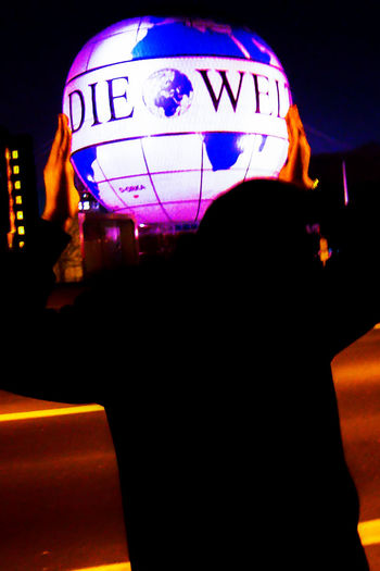 Holding The World Berlin Bright Dark Die Welt Germany Illuminated Information Lantern Multi Colored Night One Person Street Street Photography Streetphotography