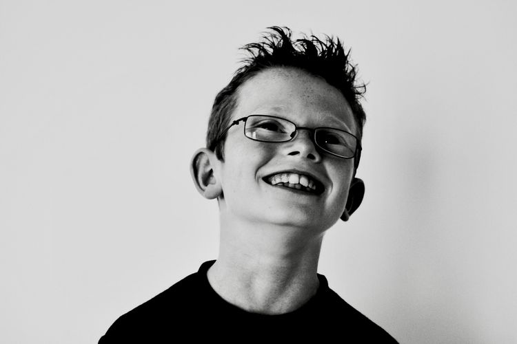 Close-up portrait of happy boy against white background