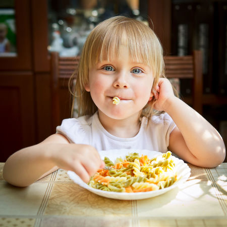 Cute little girl eating Fusilli Blond Hair Child Childhood Children Only Eat Eating Food Fusilli Girl Hungry Indoors  Looking At Camera Mealtime Nutrition One Person Pasta Plate Portrait Sitting Table Tasty