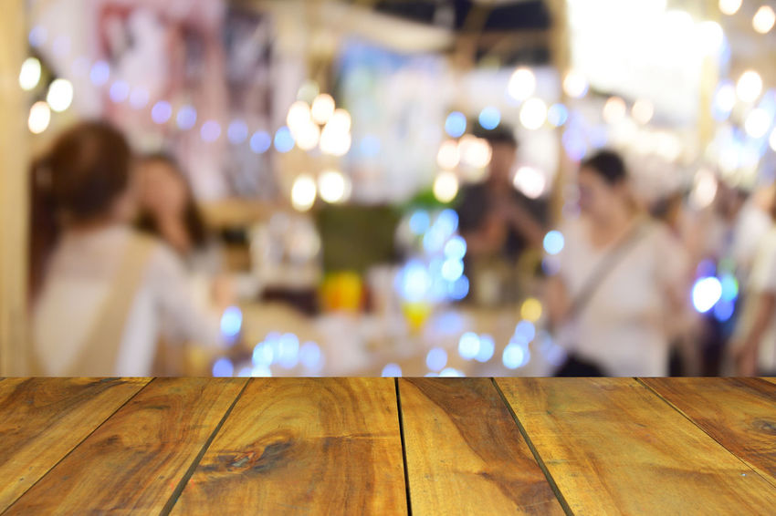 blur image wood table on food at night festival with bokeh background Business Celebration Circle City Cityscape Colors Dark Event Fashion Backgrounds Blue Blur Bokeh Building Ciub Clown Decoration Defocused Dowtown Evening Festival Festive Food Glow Group