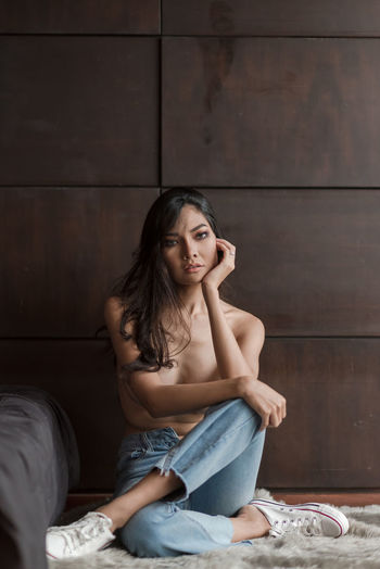 Sitting One Person Casual Clothing Full Length Indoors  Front View Real People Looking At Camera Furniture Lifestyles Young Adult Beautiful Woman Portrait Beauty Jeans Adult Wall - Building Feature Hair Women Hairstyle Contemplation