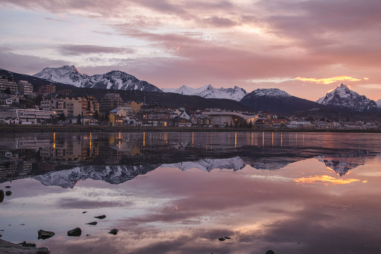 Reflection Of Buildings And Snowcapped Mountains In Lake During Sunset