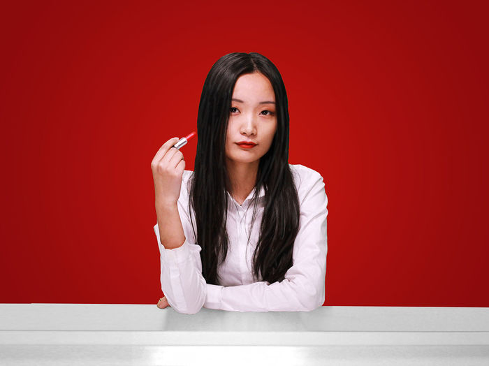 Portrait Of Young Woman With Lipstick Against Red Background