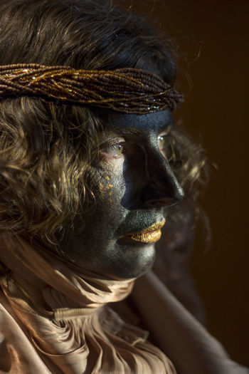 A woman with black painted face and golden clothes, party time, festival, close up portrait