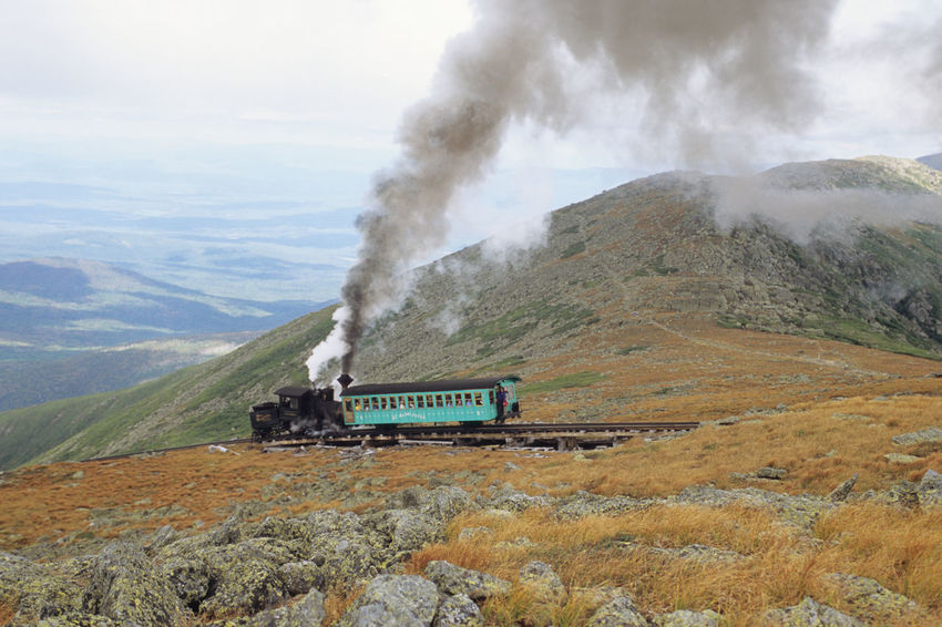 Steam Train of Mount Washington Cog Railway is pusing up Coach to the summit at good weather conditions Blue Sky White Clouds Bretton Woods Mount Washington Cog Railway Narrow Gauge Railway New Hampshire, USA Smoke Beauty In Nature Day Environment Land Land Vehicle Landscape Mode Of Transportation Motion Mountain Nature No People Non-urban Scene on the move Outdoors Power In Nature Public Transportation Scenics - Nature Sky Smoke - Physical Structure Summit Train Train - Vehicle Transportation