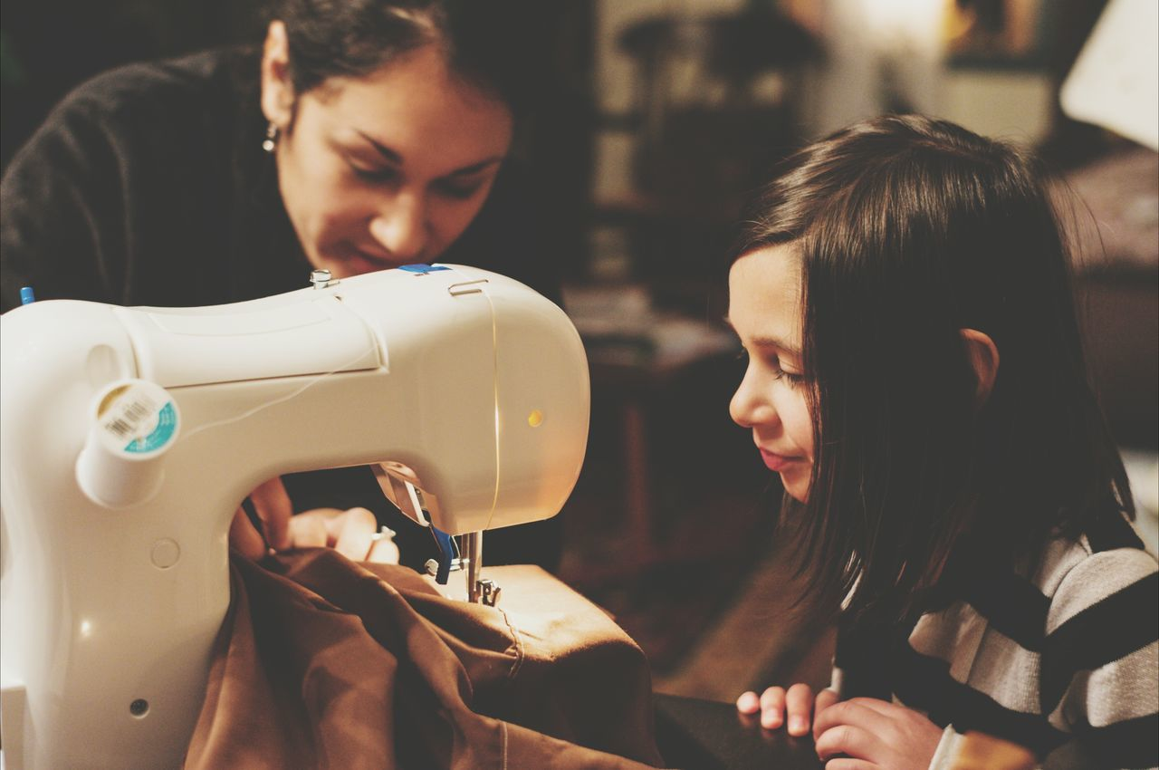 Girl looking at mother sewing fabric indoors