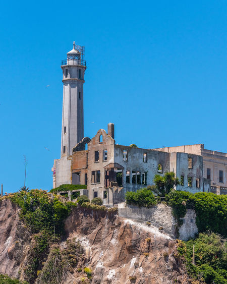 Alcatraz Built Structure Architecture Building Exterior Building Sky Blue Tower Nature Clear Sky The Past History No People Day Plant Travel Low Angle View Rock Travel Destinations Copy Space Guidance Lighthouse Outdoors