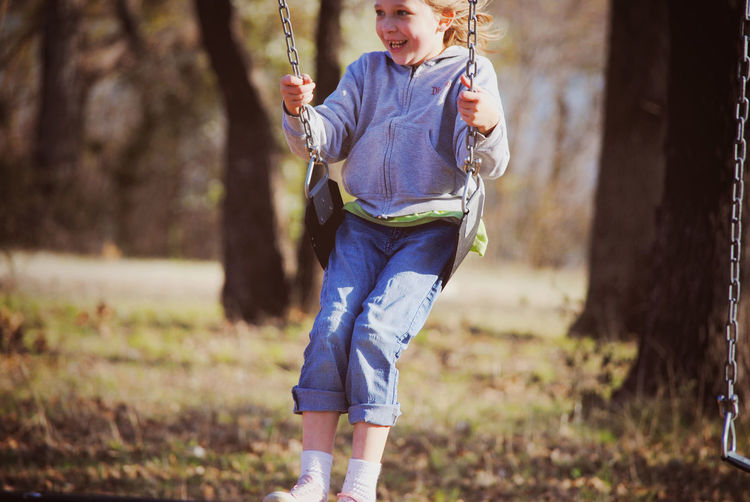 Happy girl swinging against trees