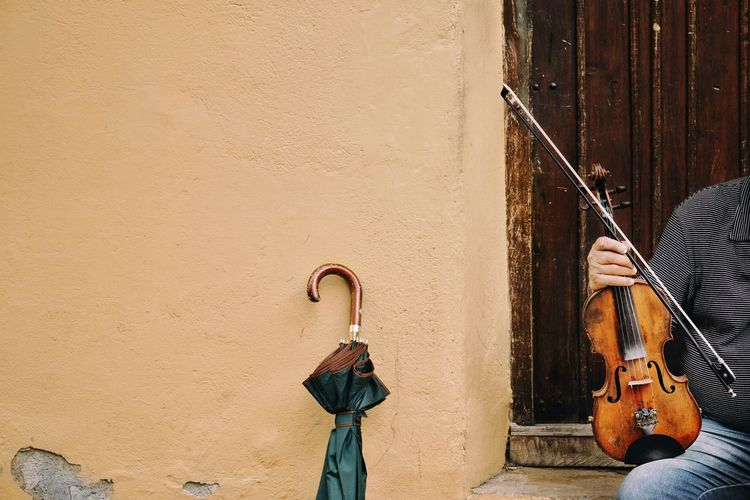 Man Holding Violin While Sitting At Door Of House