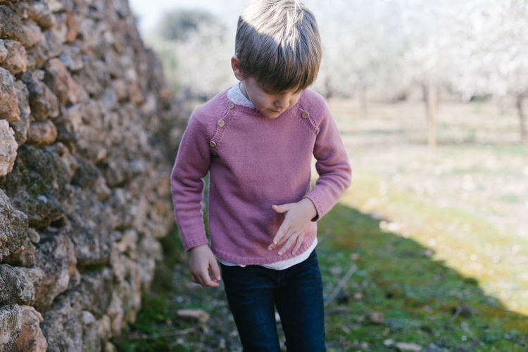 Boy standing against stone wall