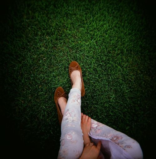 Low section of woman sitting on field at park