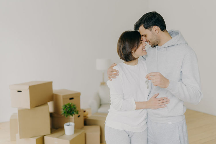 Couple embracing while standing at new home