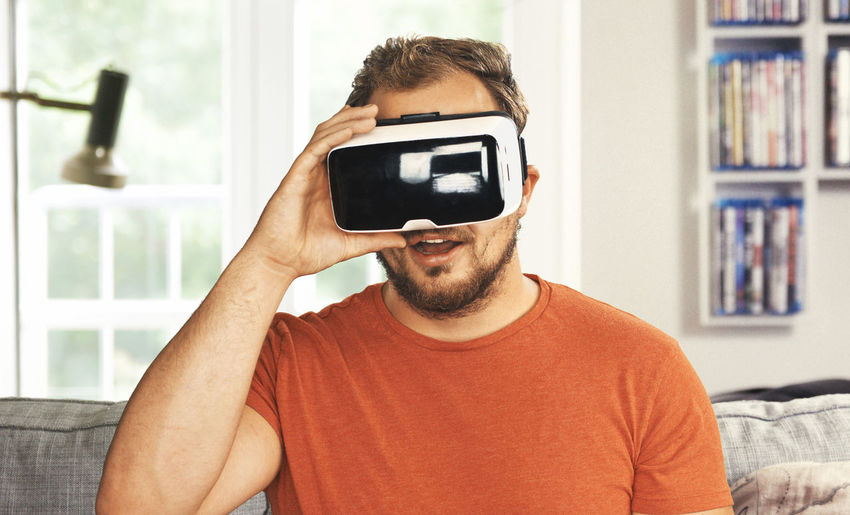 Portrait of young man using virtual reality simulator