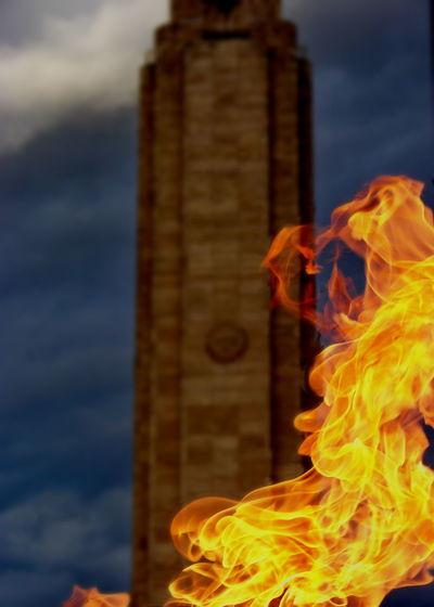 Bonfire on building against sky