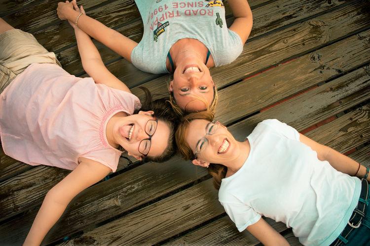 Portrait Of Happy Friends Lying On Hardwood Floor