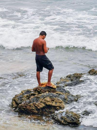 Full length of shirtless man looking at sea