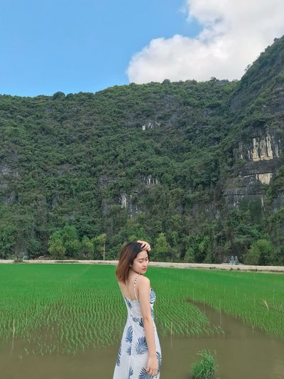 Side view of woman standing at rice paddy against mountains