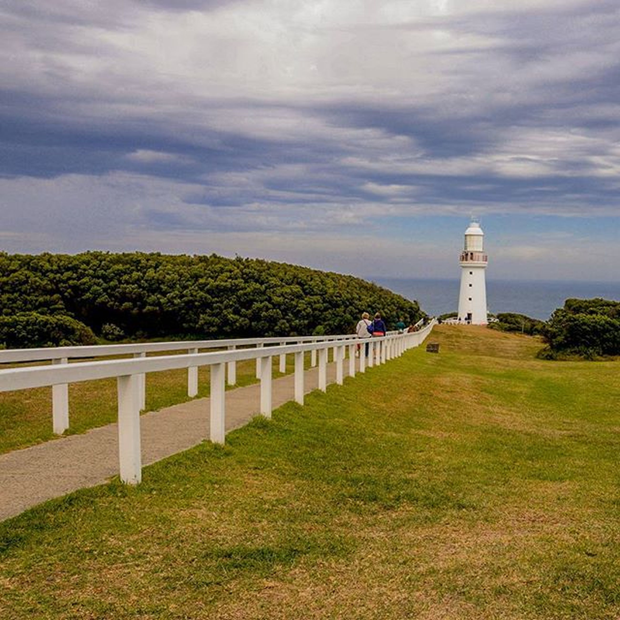 architecture, built structure, sky, lighthouse, grass, building exterior, cloud - sky, guidance, tower, tree, cloud, cloudy, protection, nature, green color, safety, water, day, direction, tranquility