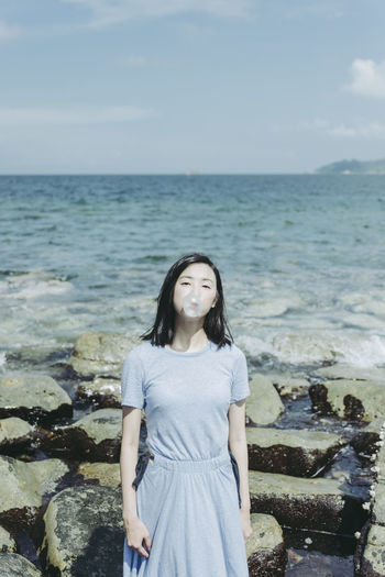 Portrait of beautiful woman blowing bubble gum while standing against rock at beach