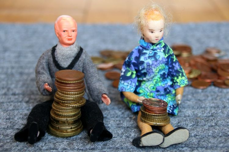 Close-Up Of Figurines With Coins On Fabric