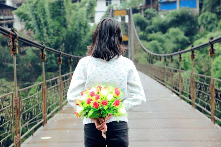 Rear View Of Woman Walking On Footbridge And Holding Bouquet
